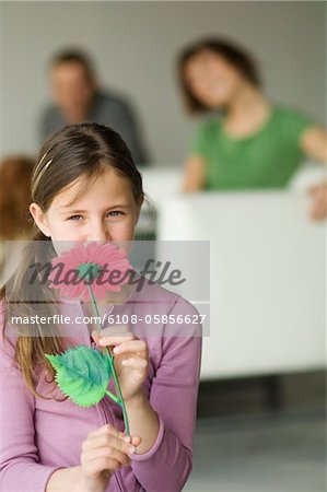 Little girl holding a plastic flower in front of her face, couple in the background Stock Photo - Premium Royalty-Free, Image code: 6108-05856627