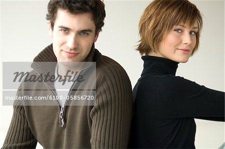 Couple sitting back to back, looking at the camera Stock Photo - Premium Royalty-Free, Image code: 6108-05856720