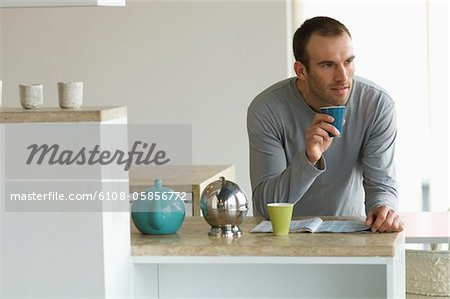 Man standing inthe kitchen, holding glass Stock Photo - Premium Royalty-Free, Image code: 6108-05856772