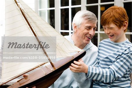 Senior man and boy holding a model boat, outdoors Stock Photo - Premium Royalty-Free, Image code: 6108-05856858