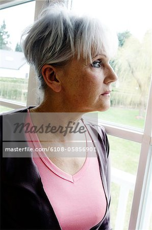 Thinking senior woman looking through a window Stock Photo - Premium Royalty-Free, Image code: 6108-05856901