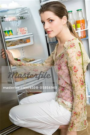 Woman crouching in front of refrigerator Stock Photo - Premium Royalty-Free, Image code: 6108-05856940