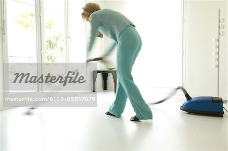 Woman vacuuming in living-room Stock Photo - Premium Royalty-Free, Image code: 6108-05857079