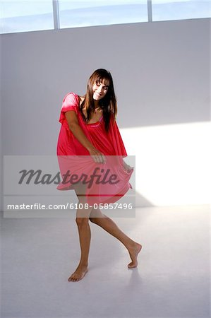 Young smiling woman dancing in red dress Stock Photo - Premium Royalty-Free, Image code: 6108-05857496