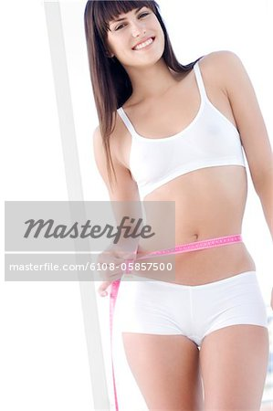 Young smiling woman measuring waist with tape measure Stock Photo - Premium Royalty-Free, Image code: 6108-05857500
