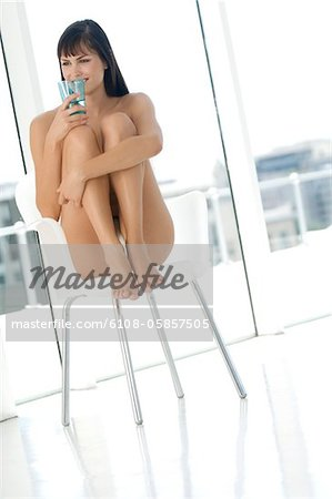 Young woman in underwear sitting on a chair, holding glass of water Stock Photo - Premium Royalty-Free, Image code: 6108-05857505