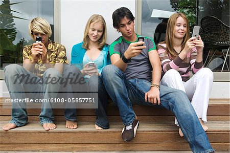 2 teenage boys and 2 teenage girls using their mobile phones