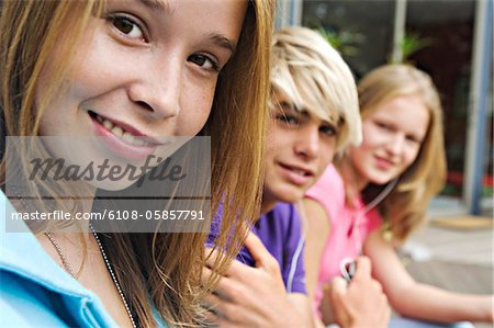 2 teenage girls and teenage boy smiling for camera Stock Photo - Premium Royalty-Free, Image code: 6108-05857791