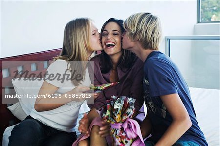 Teenage boy ang girl with gifts, kissing smiling woman Stock Photo - Premium Royalty-Free, Image code: 6108-05857813