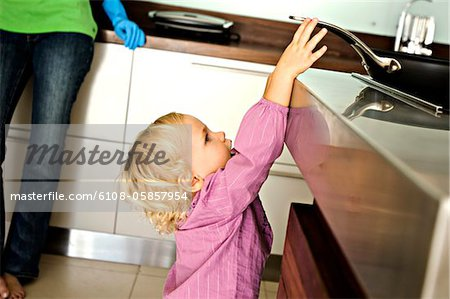 Little girl in kitchen trying to catch a frying pan on stove, indoors Stock Photo - Premium Royalty-Free, Image code: 6108-05857954