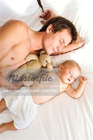 Father and baby sleeping, view from above, indoors Stock Photo - Premium Royalty-Free, Image code: 6108-05857982