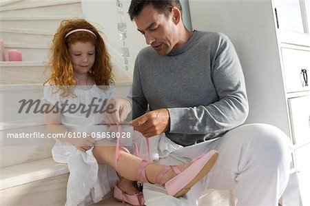 Father and daughter opening Christmas presents, girl holding a princess costume, indoors Stock Photo - Premium Royalty-Free, Image code: 6108-05858028