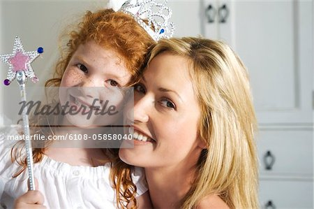 Christmas day, portrait of a mother and daughter smiling, looking at the camera, indoors Stock Photo - Premium Royalty-Free, Image code: 6108-05858040