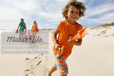 Parents and little boy walking on the beach, outdoors Stock Photo - Premium Royalty-Free, Image code: 6108-05858069