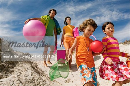 Parents and two children walking on the beach, outdoors Stock Photo - Premium Royalty-Free, Image code: 6108-05858115