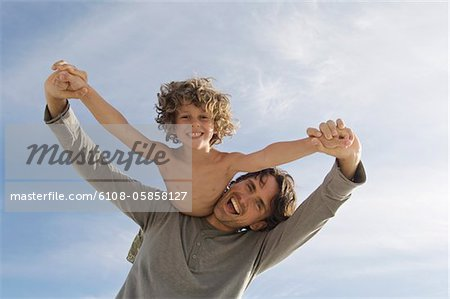 Portrait of a father carrying his son on his back, outdoors Stock Photo - Premium Royalty-Free, Image code: 6108-05858127