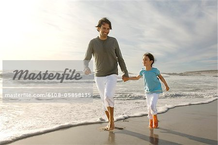 Father and daughter walking on the beach, outdoors Stock Photo - Premium Royalty-Free, Image code: 6108-05858135