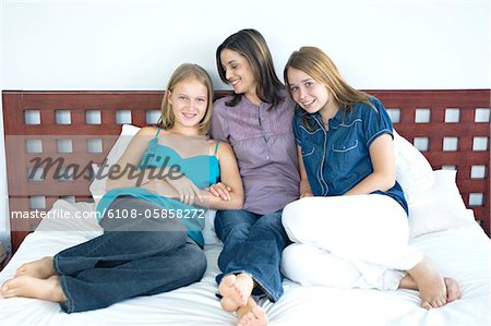Mother and two teenagers sitting on a bed, indoors Stock Photo - Premium Royalty-Free, Image code: 6108-05858272