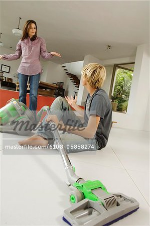 Mother and son in living room, vacuum cleaner, indoors Stock Photo - Premium Royalty-Free, Image code: 6108-05858274