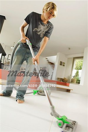 Teenager vacuuming, indoors Stock Photo - Premium Royalty-Free, Image code: 6108-05858292