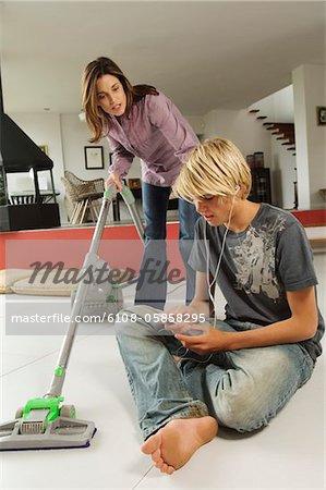 Mother vacuuming and speaking to his son, sitting on floor, indoors Stock Photo - Premium Royalty-Free, Image code: 6108-05858295