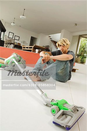 Teenager sitting on floor in living room, vacum cleaner, indoors Stock Photo - Premium Royalty-Free, Image code: 6108-05858304