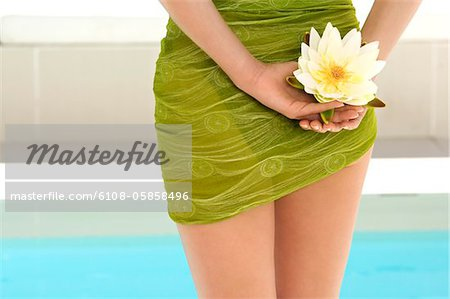 Young woman near a pool, holding a water lily, outdoors Stock Photo - Premium Royalty-Free, Image code: 6108-05858496