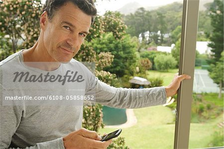 Man leaning against bay window, holding mobile phone Stock Photo - Premium Royalty-Free, Image code: 6108-05858652