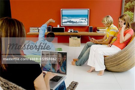 Family in living room, woman using laptop, man watching TV, 2 teens using mobile phone Stock Photo - Premium Royalty-Free, Image code: 6108-05858662