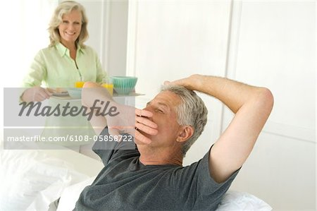Woman bringing breakfast to man yawning in bed Stock Photo - Premium Royalty-Free, Image code: 6108-05858722