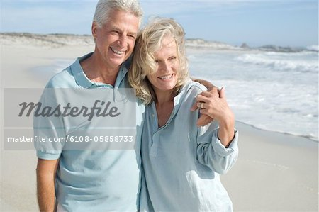 Smiling couple embracing on the beach Stock Photo - Premium Royalty-Free, Image code: 6108-05858733