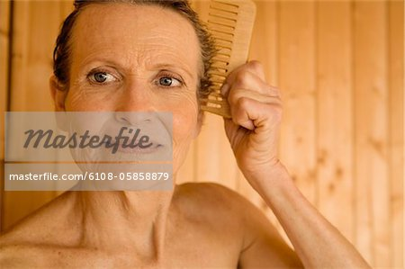 Portrait of senior woman combing her hair Stock Photo - Premium Royalty-Free, Image code: 6108-05858879
