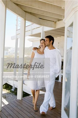 Smiling couple embracing, walking on wooden terrace Stock Photo - Premium Royalty-Free, Image code: 6108-05858937