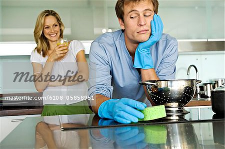 Smiling woman looking at sulking man holding sponge Stock Photo - Premium Royalty-Free, Image code: 6108-05858951