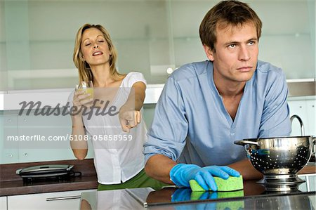 Smiling woman pointing at angry man holding sponge Stock Photo - Premium Royalty-Free, Image code: 6108-05858959