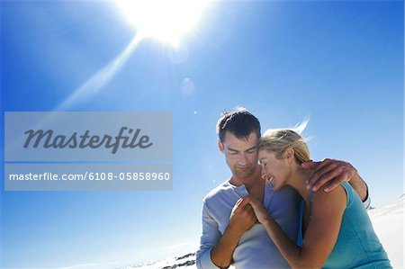 Couple embracing on the beach Stock Photo - Premium Royalty-Free, Image code: 6108-05858960