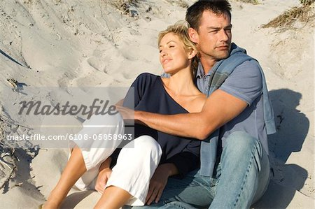 Couple embracing, sitting on the beach Stock Photo - Premium Royalty-Free, Image code: 6108-05858963