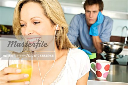 Portrait of young smiling woman holding glass of orange juice, tired man in background Stock Photo - Premium Royalty-Free, Image code: 6108-05858968