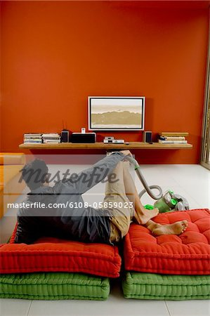 Man watching TV lying on cushions, vacuum cleaner in front of him Stock Photo - Premium Royalty-Free, Image code: 6108-05859023