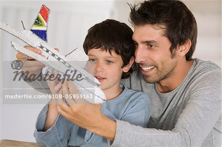 Father and son playing with model aeroplane Stock Photo - Premium Royalty-Free, Image code: 6108-05859163