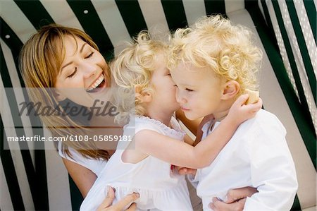 Mother and 2 children on a swing chair Stock Photo - Premium Royalty-Free, Image code: 6108-05859181