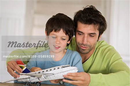 Father and son playing with model aeroplane Stock Photo - Premium Royalty-Free, Image code: 6108-05859199