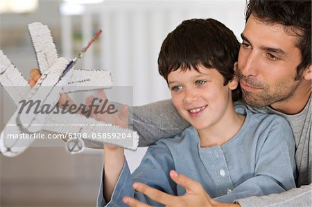 Father and son playing with model aeroplane Stock Photo - Premium Royalty-Free, Image code: 6108-05859204