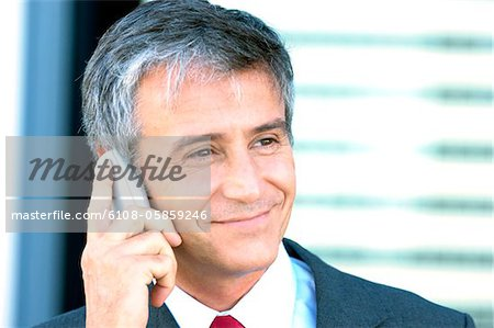 Mature businessman using mobile phone, close-up Stock Photo - Premium Royalty-Free, Image code: 6108-05859246