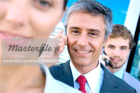 Business people using mobile phones, smiling Stock Photo - Premium Royalty-Free, Image code: 6108-05859552