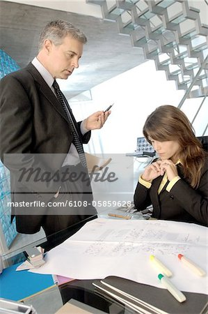 Businessman discussing with colleague in office Stock Photo - Premium Royalty-Free, Image code: 6108-05859628