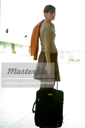 Businesswoman standing with her luggage at an airport Stock Photo - Premium Royalty-Free, Image code: 6108-05859669