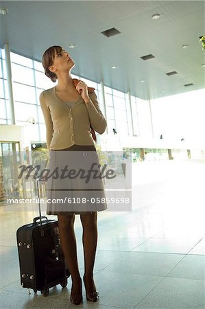 Businesswoman standing with her luggage at an airport lounge Stock Photo - Premium Royalty-Free, Image code: 6108-05859698