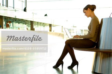 Side profile of a businesswoman using a laptop at an airport lounge Stock Photo - Premium Royalty-Free, Image code: 6108-05859712
