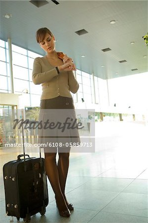 Low angle view of a businesswoman checking the time at an airport Stock Photo - Premium Royalty-Free, Image code: 6108-05859713